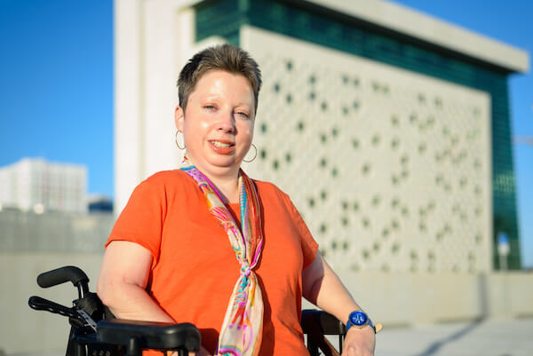 Photo of author Heidi Johnson-Wright, wearing a red, short-sleeved top, a colorful scarf and hoop earrings. She's sitting in a wheelchair, smiling.
