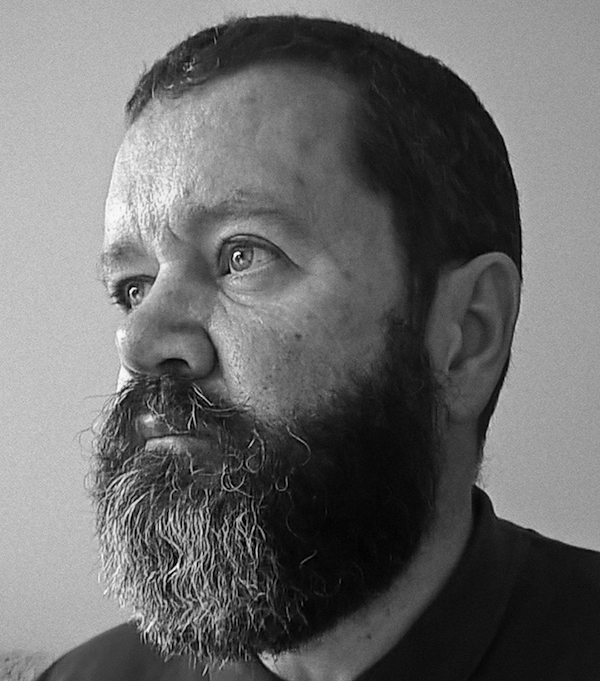 A black and white profile photo of Oleb Books author Nigel David Kelly, a man in his mid-50s with a full, well-trimmed beard.