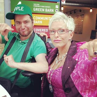 Oleb Books author Andrew Gurza is sitting in a wheelchair wearing a green shirt and hat and is posing happily alongside his mother.